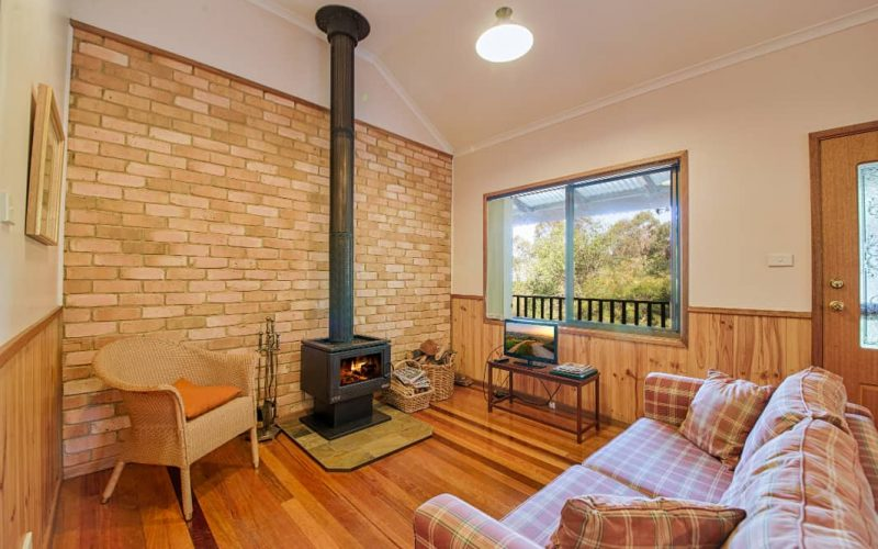 McDonald Cottage living area with fireplace at Glen Ayr Cottages