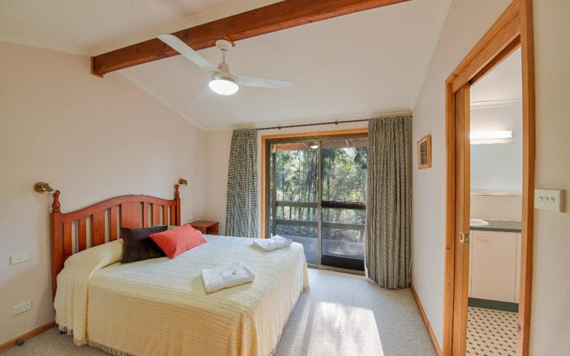 Stewart Cottage bedroom with queen bed and en-suite at Glen Ayr Cottages