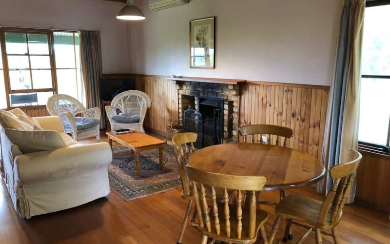 Sutherland Cottage living area with open fireplace at Glen Ayr Cottages
